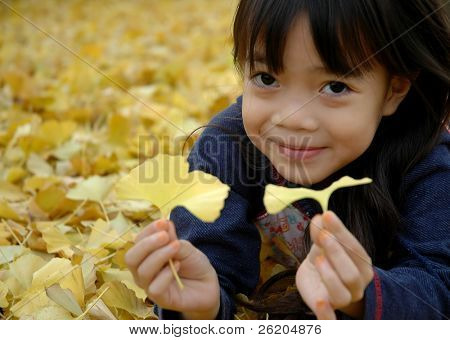 Little girl playing with ginkgo leaves