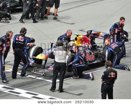 SEPANG, MALAYSIA - APRIL 4: Pit crews prepare Mark Webber's car of Red Bull Racing Team at Malaysian F1 Grand Prix April 4, 2010 at Sepang International Circuit in Malaysia.