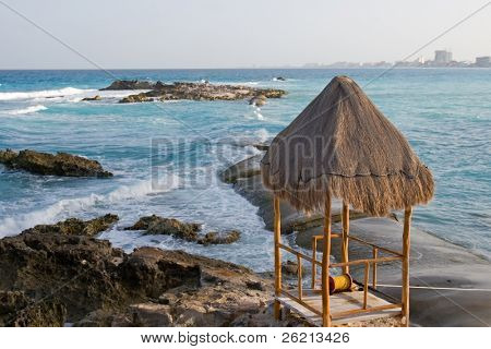 Thatch Hut on a rocky peninsula on a tropical beach at a luxury resort hotel in cancun mexico