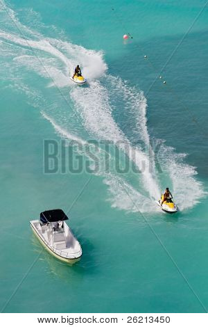 Seadoos, jetskis, and watercraft on the blue caribbean ocean at a resort hotel in cancun mexico