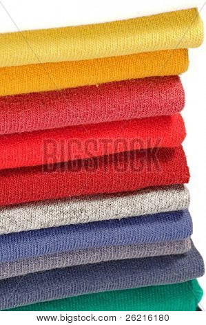 Stack of colored tee shirts on a shelf