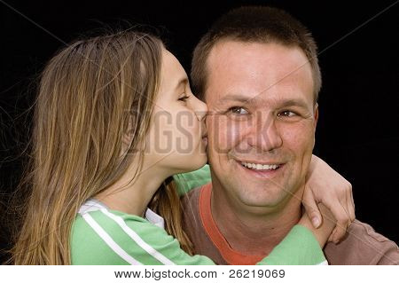 cute caucasian american girl kissing father on cheek