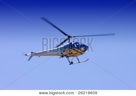 Helicopter frozen in time with rotors captured with illustrating some movement at the tips