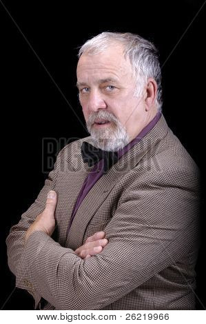 older businessman with a trimmed beard in a sportscoat and  bow-tie isolated on black looking professorial