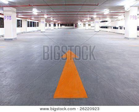 Empty Parking Garage With Yellow Arrow