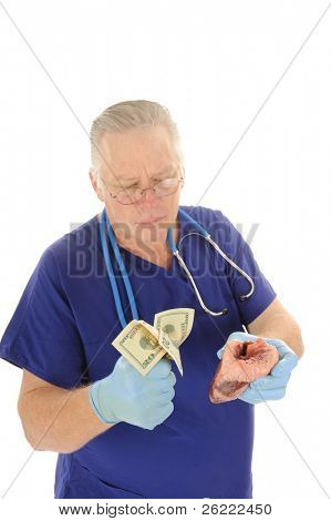 Doctor holding fist full of money repesenting the escalating costs of medical attention, and or body parts for sale