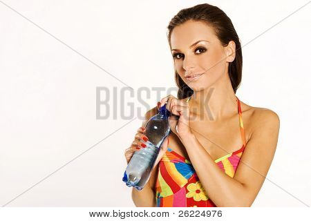 a beautiful brunette girl wearing colorful dress holding a big bottle of mineral water on white background