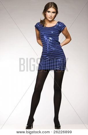 beautiful blond model in blue lucid dress posing on grey background