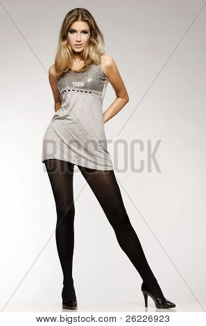 beautiful blond model in grey lucid dress posing on grey background