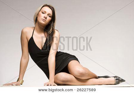beautiful blond model lying on grey background wearing black mini dress