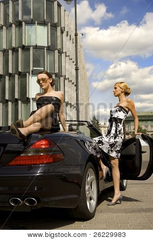 two pretty woman in black exclisive car