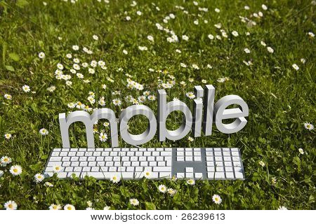'mobile' text and modern keyboard on green grass in garden, concept