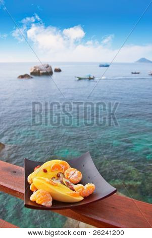 Plate full of exotic fruits on the parapet of a sea view restaurant