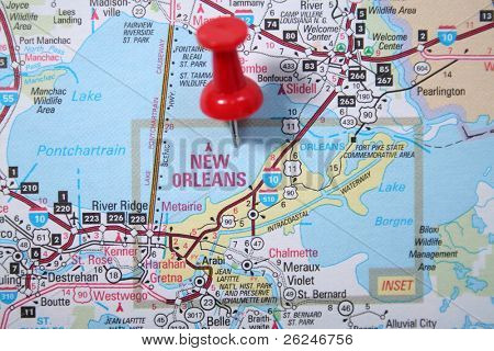 Atlas map with the city of New Orleans pinpointed with a red thumb tack.