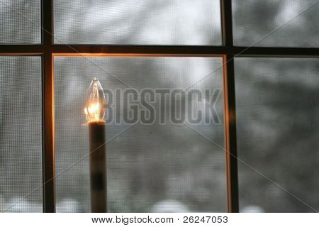 welcoming Christmas candle burns in the window looking out to a fresh snowfall
