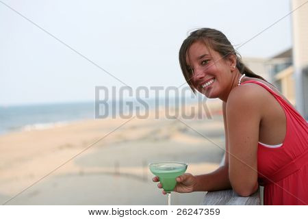 Attractive female having a cocktail while looking at the ocean