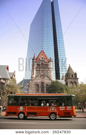 Sightseeing bus passes the Trinity Church and the John Hancock Building in Boston, massachusetts