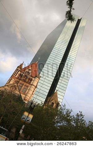 Contrast between old and new architecture in Boston, Massachusetts.  The Trinity Church is in the foreground and the john Hancock Building is in the background