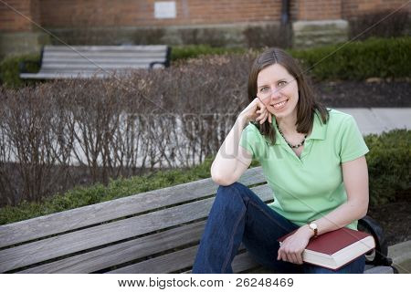 College student sitting on a bench on campus