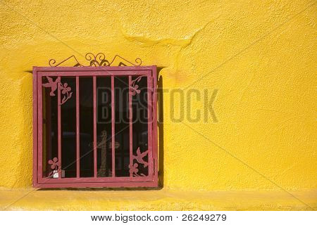 red window in a yellow wall
