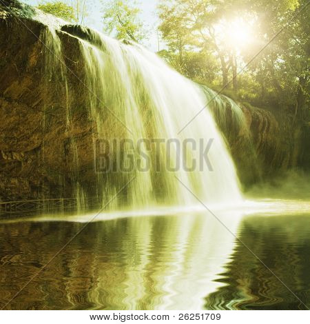 Waterfall pool in rain forest and sunlight
