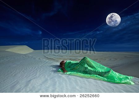 Beautiful woman sleeping in desert under moonlight
