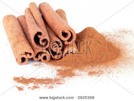 Cinnamon Powder And Sticks On White