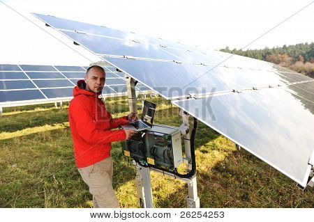 Man working with laptop at solar panels field