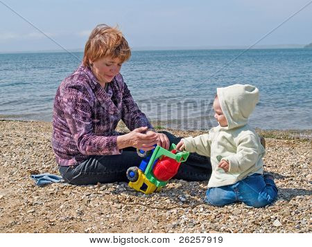 happy family of kid and mother playing in the spring park on sea beach with toy