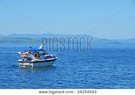 motor yacht sailing against the rocky coast