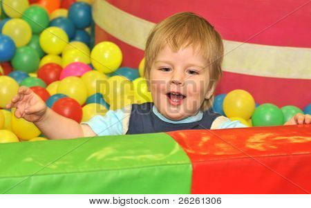 kid playing with colored balls