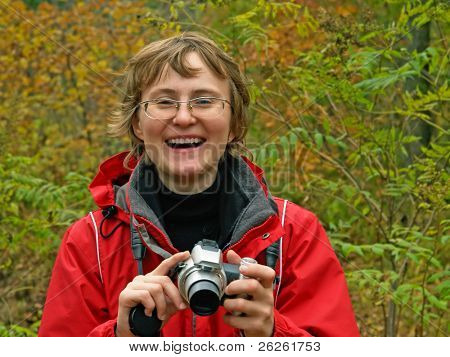 smiling hiking girl in fall forest with digital camera in hands