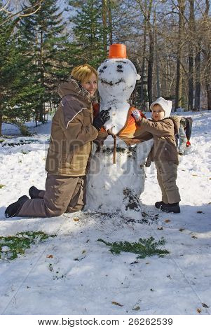 happy family of mother with kid making snowman