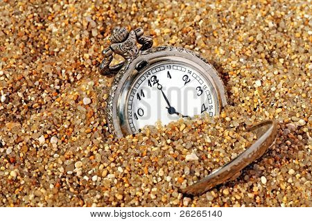 vintage pocket watch in the sand. time concept