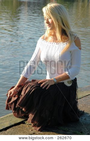 young blonde woman by the river in a park