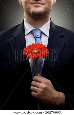 closeup portrait of smiling businessman holding red flower