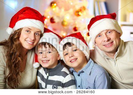 Portrait of four happy family members in Santa caps looking at camera