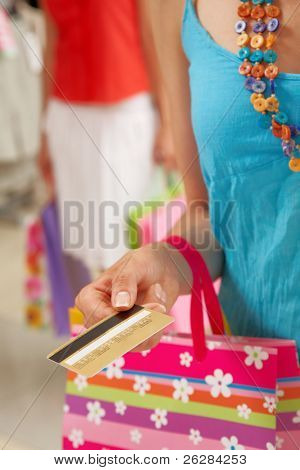 Image of woman?s hand giving plastic card in the mall