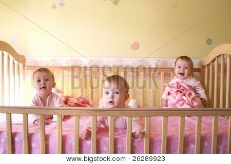 Little Baby Girls in crib together - Triplets