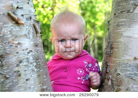 Little Baby Girl posing by a tree in summer