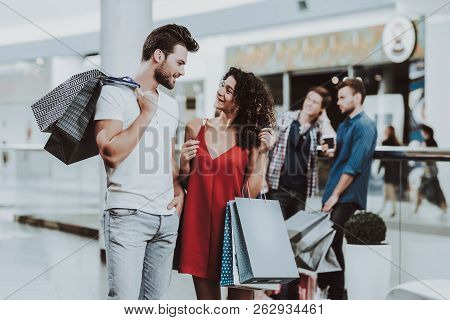 poster of Young Couple With Packages After Shopping In Mall. Looking Into Package. Shopping Concept. Girl In R