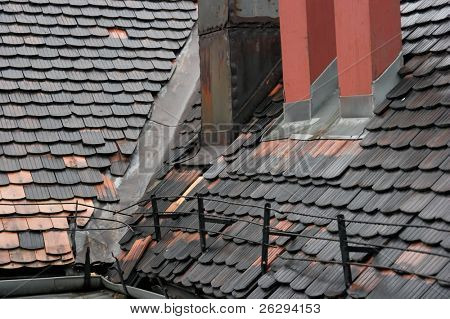 Roof of an old building with dark tiles and chimneys