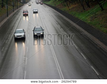 Cars passing by on a wet rainy road