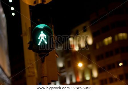 Green traffic light for pedestrians in a city by night