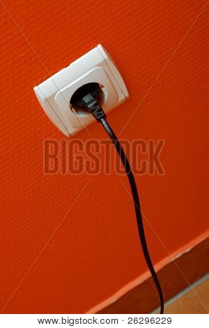 Electric cable plugged into the wall outlet