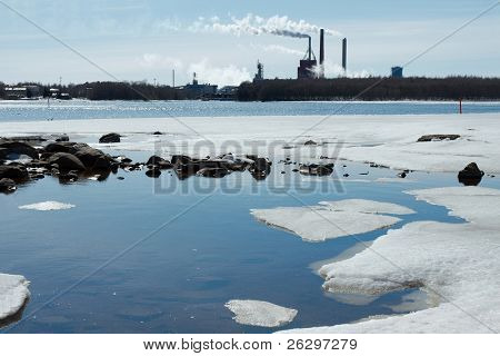 Smoking industrial plant and melting ice