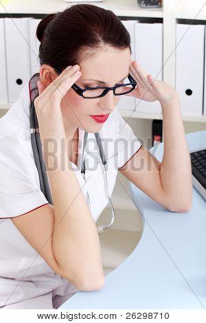 Pretty caucasian sitting female doctor having headache in the office.
