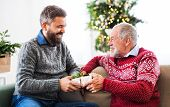 A Senior Father And Adult Son With A Present Sitting On A Sofa At Christmas Time. poster