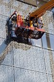 image of boom-truck  - Construction workers working with building facade elements on bucket truck extension arm - JPG