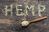 Word Hemp Made Of Hemp Seeds On Old Wooden Background. Organic Blanched Hemp Seeds In A Spoon On Rus poster